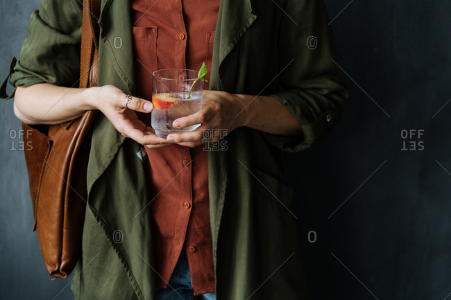 Woman holding a clear cocktail with peach