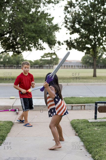 Boy and girl pretending to have a sword fight