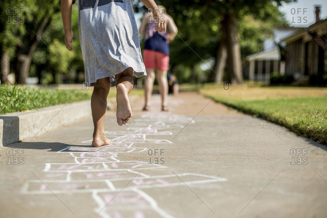 Barefoot girl playing hopscotch on the sidewalk