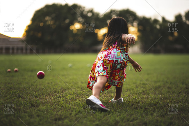 Back view of a girl tossing a ball on a field