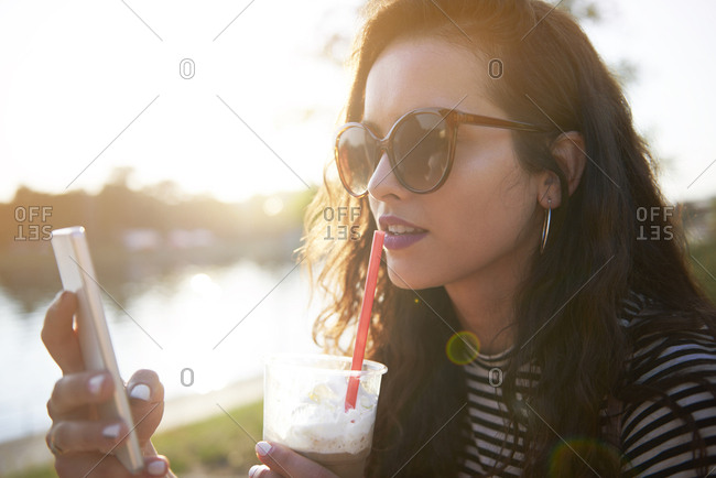 Stylish young woman with cell phone and takeaway drink outdoors at sunset