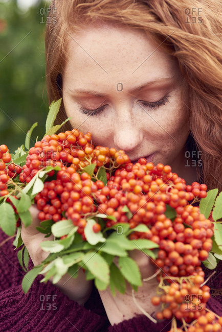Portrait of freckled redheaded young woman with rowanberries