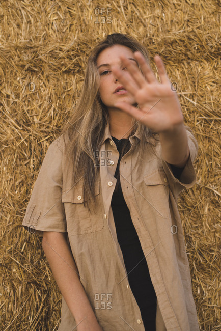 Young woman standing in front of hay bales making rejecting hand gesture- portrait