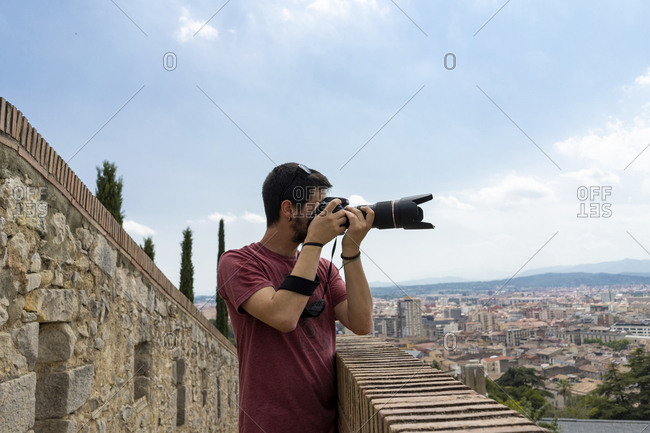 Spain- Girona- man at the castle taking picture of the city