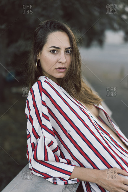 610f77aaf1 Portrait of woman wearing unbuttoned striped shirt stock photo - OFFSET