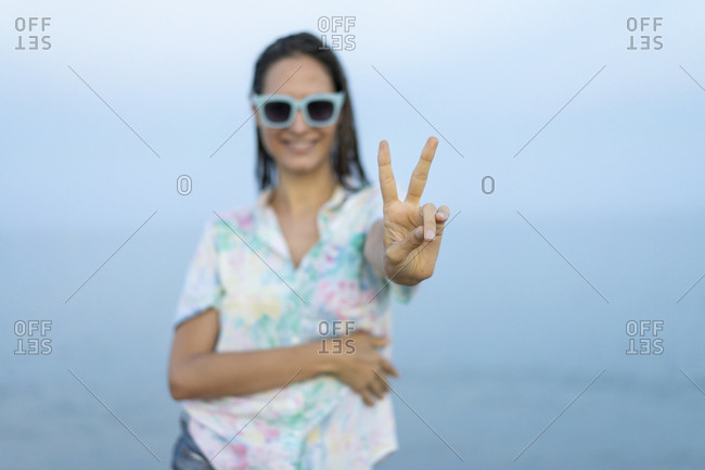 Smiling woman showing victory sign- close-up