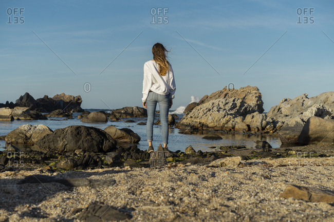 Woman looking sitting on rocks- looking at the sea