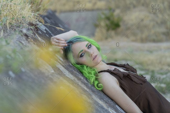 Portrait of young woman with dyed green hair and eyebrows in nature