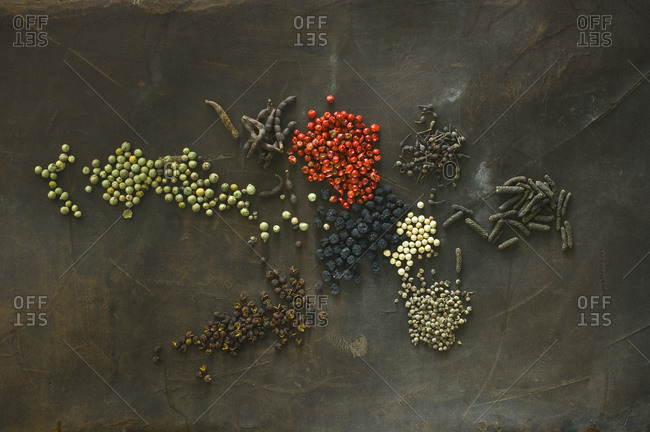 Various sorts of pepper on brown background