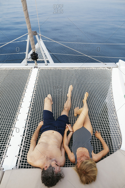 Mature couple on a sailing trip lying on trampoline- relaxing