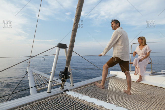 Mature couple standing on catamaran trampoline- enjoying their sailing trip