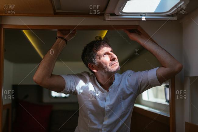 Mature man standing in catamaran cabin- looking up through hatch