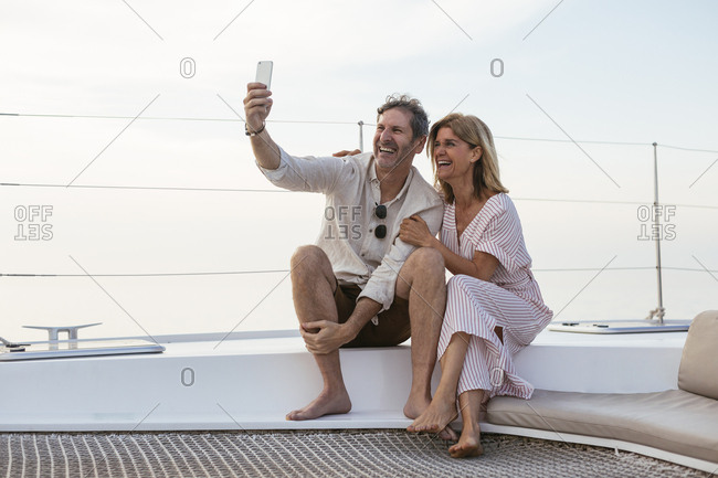 Happy couple on a sailing trip taking selfies