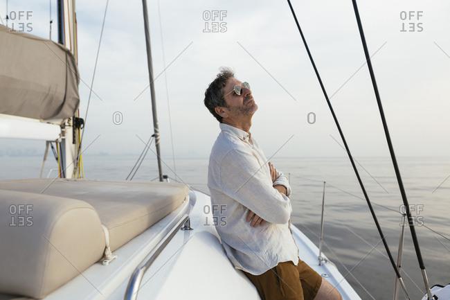 Mature man on catamaran with arms crossed- enjoying the breeze