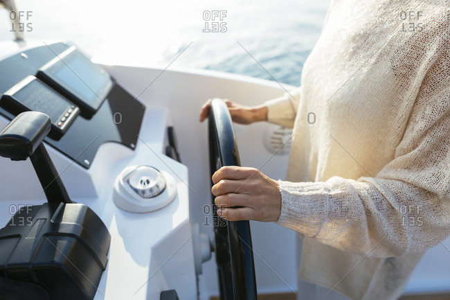 Mature woman navigating catamaran on a sailing trip