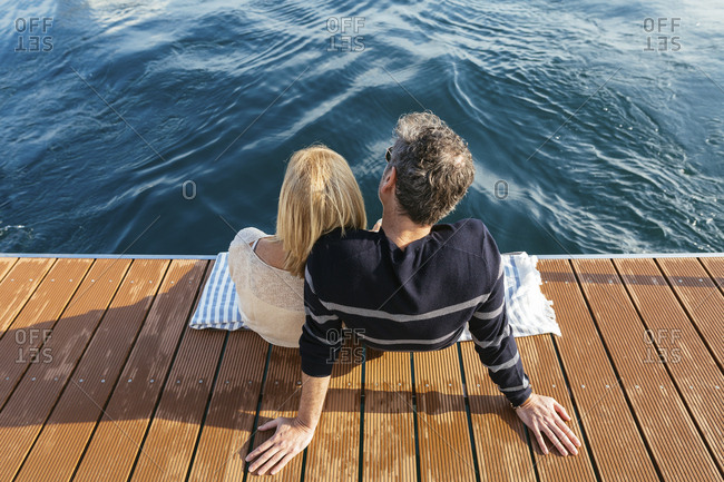 Mature couple sitting on jetty- relaxing at the sea