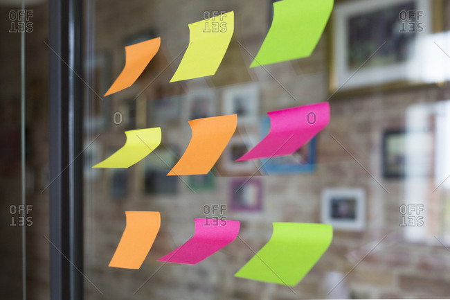 Adhesive notes on glass wall in office