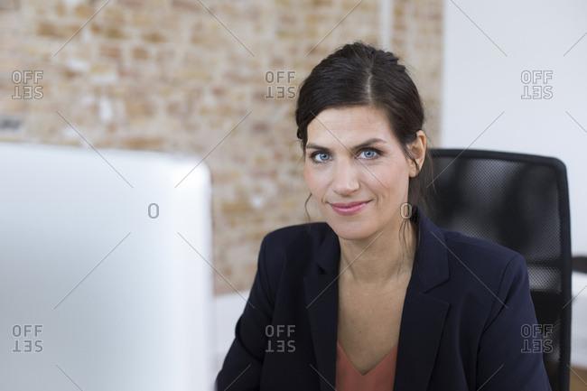 Portrait of confident businesswoman at desk in office