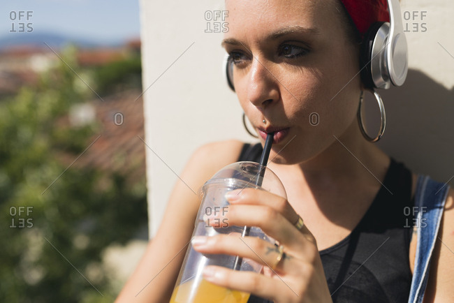 Portrait of young woman with headphones drinking soft drink