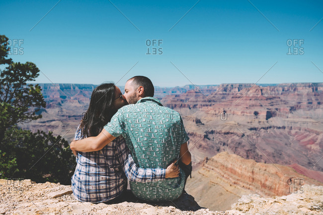 USA- Arizona- Grand Canyon National Park- back view of kissing couple sitting side by side