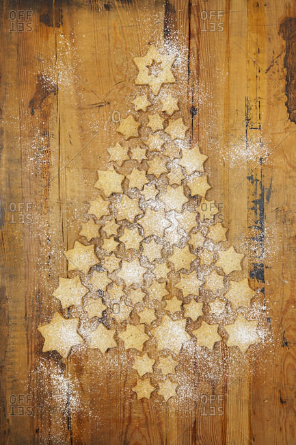 Star-shaped biscuits forming Christmas Tree on wooden  background