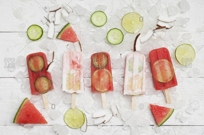 Homemade watermelon and coconut cream ice lollies with lime and cucumber slices- fresh coconut chips on ice cubes