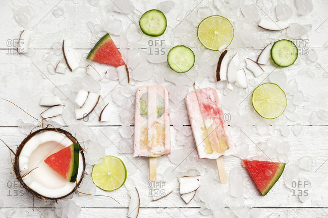 Homemade watermelon coconut ice lollies with lime and cucumber slices- fresh coconut and watermelon pieces on ice cubes