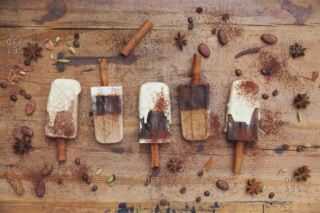 Homemade coffee and white chocolate ice lollies with winter spices on wooden background
