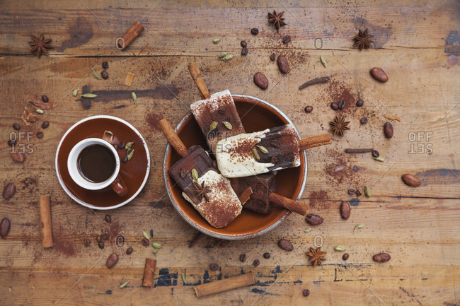 Homemade espresso and white chocolate ice lollies with winter spices and cup of espresso on wooden background