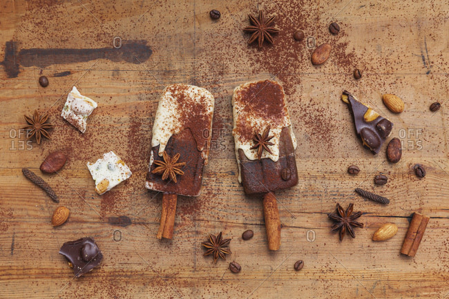 Homemade espresso and white chocolate ice lollies with winter spices on wooden background