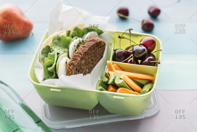 Healthy school food in a lunch box- vegetarian sandwich with cheese- lettuce- cucumber- egg and cress- sliced carrot and celery- cherries and pear
