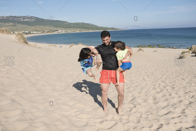 Father playing with his son and daughter at the beach- having fun