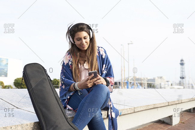 Spain- Barcelona- portrait of woman with guitar case and headphones looking at cell phone