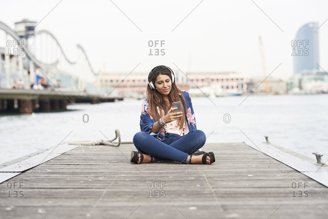 Spain- Barcelona- portrait of content woman with headphones sitting on jetty looking at cell phone