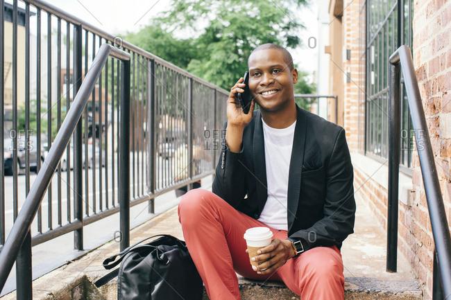USA- NYC- Brooklyn- Man waiting on stairs- using smartphone