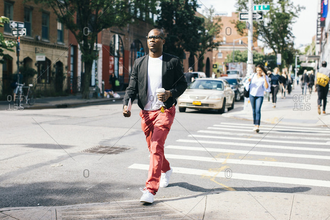 USA- NYC- Brooklyn- Man walking in the street- holding cup of coffee