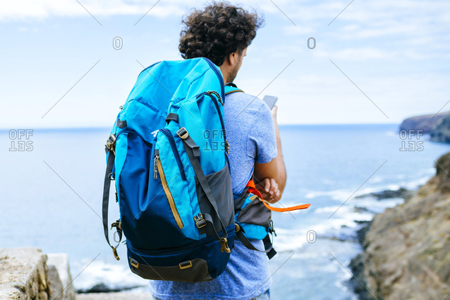 Spain- Canary Islands- Gran Canaria- Close-up of man with backpack using mobile phone