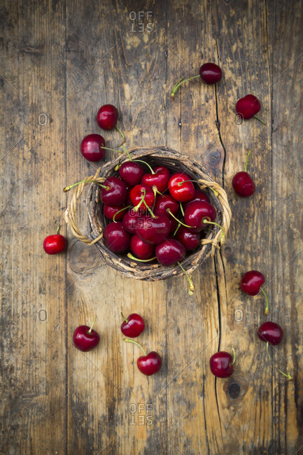 Wicker basket of cherries on wood