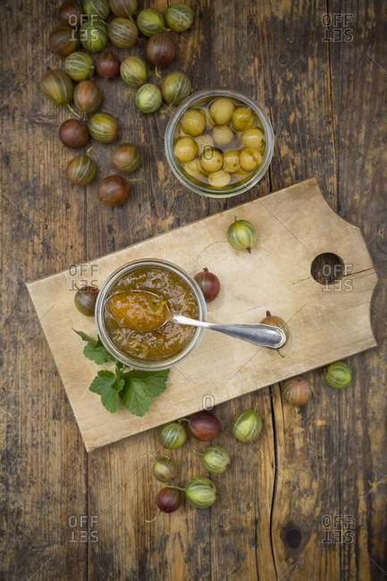 Jar of gooseberry jam- gooseberries and glass of preserved gooseberries on wood