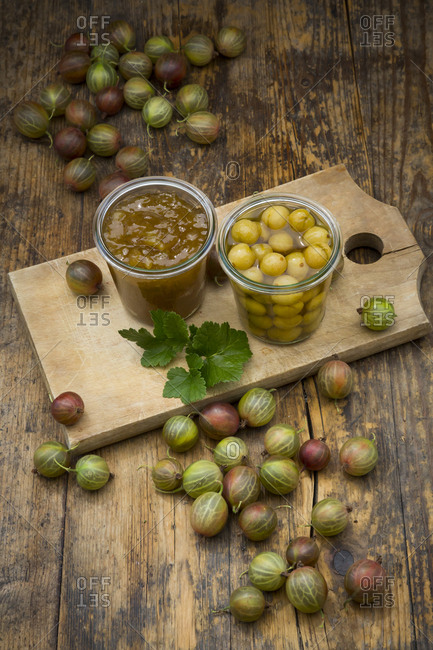 Jar of gooseberry jam- gooseberries and glass of preserved gooseberries on wooden board