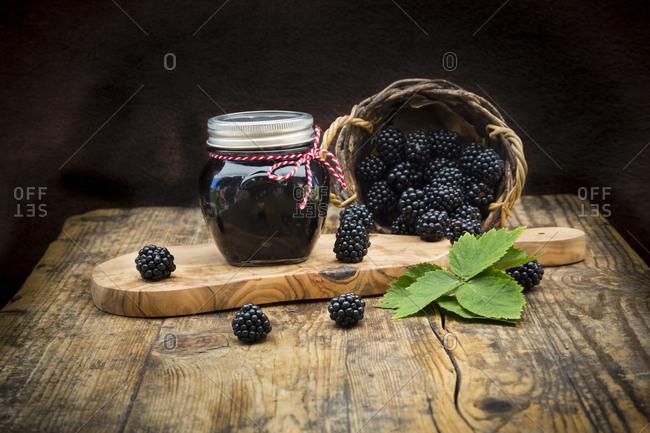 Glass of homemade blackberry jelly and blackberries on wood