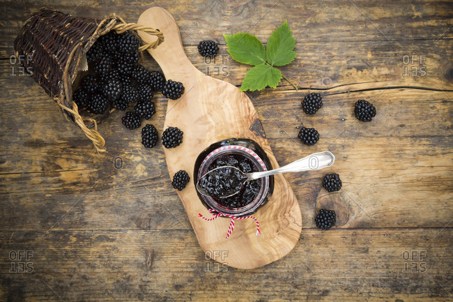 Glass of blackberry jelly and blackberries on wood