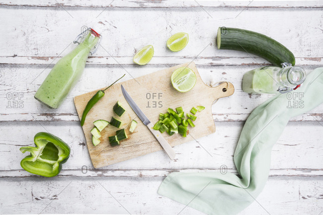 Glass bottles of homemade green Gazpacho and ingredients