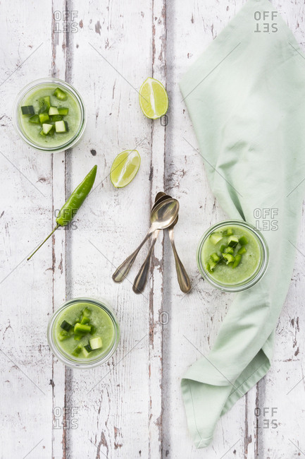 Three glasses of homemade green Gazpacho and ingredients
