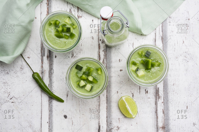Three glasses and a bottle of homemade green Gazpacho