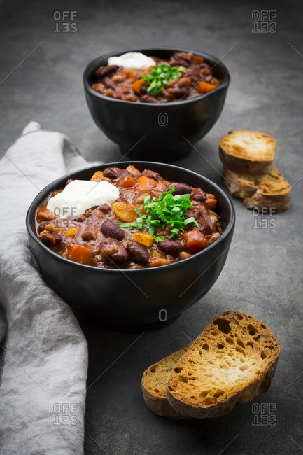 Two bowls of Chili con Carne with fresh coriander and sour cream