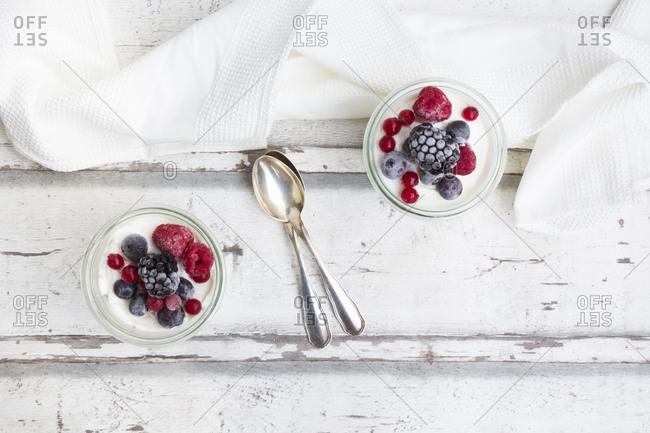 Two glasses of Greek yogurt with frozen berries