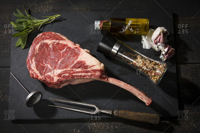 Raw tomahawk steak and ingredients