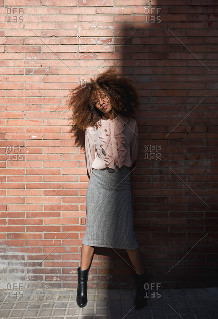 Portrait of beautiful young woman with afro hairdo at brick wall in sunshine