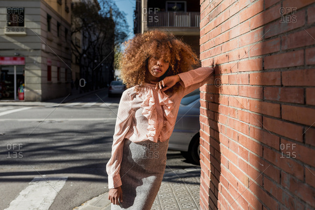 Portrait of beautiful young woman with afro hairdo leaning against brick wall in the city